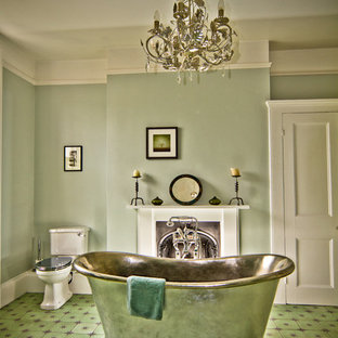 This is an example of a victorian bathroom in Sussex with a freestanding bath, a two-piece toilet, green walls and green floors.