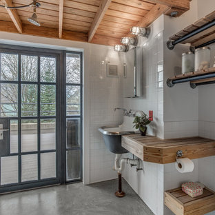 Example of an urban white tile concrete floor bathroom design in Boston with wood countertops, open cabinets, a wall-mount sink and brown countertops