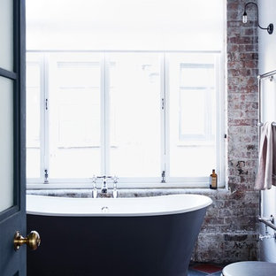 This is an example of a medium sized industrial family bathroom in London with shaker cabinets, distressed cabinets, a freestanding bath, a corner shower, a one-piece toilet, white walls, ceramic flooring and a trough sink.