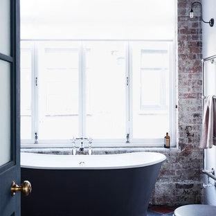 Foto de cuarto de baño infantil, industrial, de tamaño medio, con armarios estilo shaker, puertas de armario con efecto envejecido, bañera exenta, ducha esquinera, sanitario de una pieza, paredes blancas, suelo de baldosas de cerámica y lavabo de seno grande