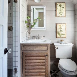 Imagen de cuarto de baño con ducha, campestre, pequeño, con sanitario de dos piezas, baldosas y/o azulejos blancos, baldosas y/o azulejos de cemento, suelo multicolor, ducha con puerta con bisagras, encimeras blancas, armarios tipo mueble, puertas de armario de madera clara, paredes beige y lavabo integrado