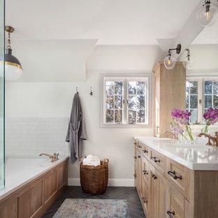 Großes Landhaus Badezimmer En Suite mit hellen Holzschränken, weißen Fliesen, Metrofliesen, weißer Wandfarbe, Unterbauwaschbecken, grauem Boden, Falttür-Duschabtrennung, weißer Waschtischplatte, Schrankfronten im Shaker-Stil und Eckbadewanne in Denver