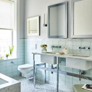Idee per una stanza da bagno chic con vasca sottopiano, piastrelle blu, piastrelle di vetro, pareti grigie, pavimento con piastrelle a mosaico, lavabo sottopiano, pavimento grigio e top bianco