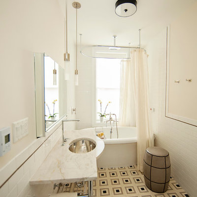 Freestanding bathtub - mid-sized contemporary 3/4 white tile and subway tile linoleum floor freestanding bathtub idea in New York with an undermount sink, marble countertops, a wall-mount toilet and beige walls