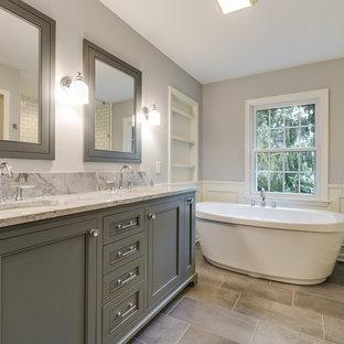 Foto på ett stort lantligt flerfärgad en-suite badrum, med luckor med profilerade fronter, grå skåp, ett fristående badkar, en dusch i en alkov, grå väggar, klinkergolv i porslin, ett undermonterad handfat, granitbänkskiva, grått golv och dusch med gångjärnsdörr