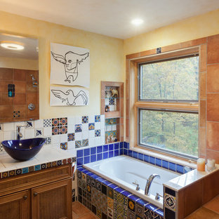 Example of an eclectic blue tile, multicolored tile and orange tile drop-in bathtub design in New York with recessed-panel cabinets, medium tone wood cabinets, yellow walls, a vessel sink and tile countertops