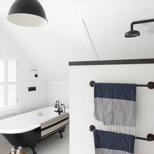 ニューヨークの小さいインダストリアルスタイルのおしゃれなマスターバスルーム (猫足バスタブ、白いタイル、セラミックタイル、白い壁、塗装フローリング) の写真