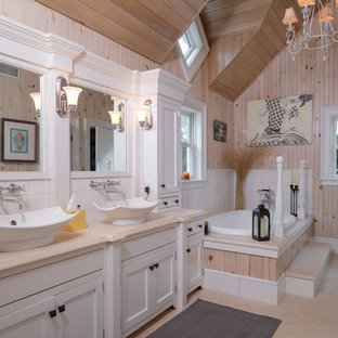 This is an example of a country bathroom in New York with shaker cabinets, white cabinets, a drop-in tub, pink walls, a vessel sink, beige floor and beige benchtops.