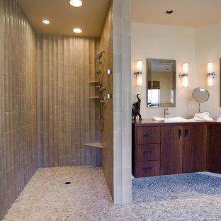 Bild på ett vintage brun brunt badrum, med ett fristående handfat, släta luckor, skåp i mörkt trä, träbänkskiva, en öppen dusch, beige kakel, porslinskakel, klinkergolv i småsten och med dusch som är öppen