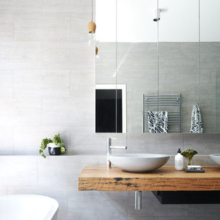 Photo of a modern master bathroom in Melbourne with a freestanding tub, gray tile, grey walls, ceramic floors, a vessel sink, wood benchtops and grey floor.