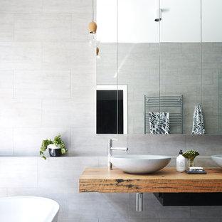 На фото: главные ванные комнаты в стиле модернизм с отдельно стоящей ванной, серой плиткой, серыми стенами, полом из керамической плитки, настольной раковиной, столешницей из дерева, серым полом и коричневой столешницей