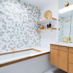 Imagen de cuarto de baño infantil, vintage, de tamaño medio, con armarios con paneles lisos, puertas de armario de madera clara, bañera encastrada sin remate, combinación de ducha y bañera, baldosas y/o azulejos grises, baldosas y/o azulejos multicolor, baldosas y/o azulejos blancos, baldosas y/o azulejos en mosaico, paredes blancas, lavabo bajoencimera, suelo gris, encimeras blancas, encimera de acrílico y ducha abierta