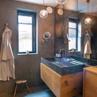 Modelo de cuarto de baño principal, ecléctico, pequeño, con armarios con paneles lisos, puertas de armario de madera oscura, bañera encastrada, combinación de ducha y bañera, sanitario de pared, baldosas y/o azulejos marrones, baldosas y/o azulejos de cerámica, paredes marrones, suelo de baldosas de cerámica, encimera de mármol, suelo gris, encimeras negras y lavabo suspendido