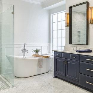 Modelo de cuarto de baño principal, clásico renovado, con armarios con paneles con relieve, puertas de armario azules, bañera exenta, paredes blancas, suelo blanco y encimeras blancas