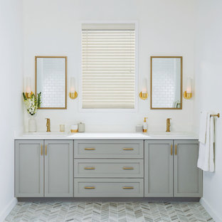 Example of a mid-sized transitional master gray floor and porcelain floor bathroom design in New York with shaker cabinets, gray cabinets, white walls, a drop-in sink, quartz countertops and white countertops