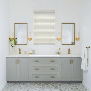 Diseño de cuarto de baño principal, tradicional renovado, de tamaño medio, con armarios estilo shaker, puertas de armario grises, paredes blancas, suelo gris, suelo de baldosas de porcelana, lavabo encastrado, encimera de cuarzo compacto y encimeras blancas