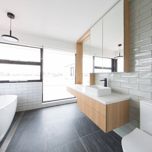 Inspiration for a contemporary 3/4 bathroom in Sydney with flat-panel cabinets, medium wood cabinets, a freestanding tub, a one-piece toilet, white tile, ceramic tile, white walls, a vessel sink and black floor.