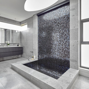 This is an example of a large contemporary master bathroom in Sydney with gray tile, marble floors, grey floor, flat-panel cabinets, grey cabinets, an undermount tub, grey walls and white benchtops.