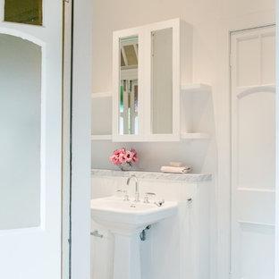 Immagine di una stanza da bagno con doccia vittoriana di medie dimensioni con ante di vetro, ante bianche, vasca freestanding, doccia aperta, WC sospeso, piastrelle bianche, pareti bianche, pavimento in gres porcellanato, lavabo a colonna, top in marmo, pavimento bianco e doccia aperta