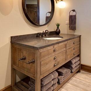 Diseño de cuarto de baño con ducha, rústico, de tamaño medio, con armarios tipo mueble, puertas de armario de madera en tonos medios, paredes beige, suelo de madera clara, lavabo bajoencimera, encimera de cemento y suelo marrón