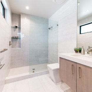 Idéer för ett mellanstort klassiskt vit badrum med dusch, med släta luckor, grå skåp, en öppen dusch, en toalettstol med hel cisternkåpa, grå kakel, keramikplattor, vita väggar, klinkergolv i porslin, ett undermonterad handfat, bänkskiva i kvarts, vitt golv och med dusch som är öppen