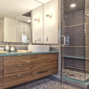 Diseño de cuarto de baño principal, vintage, de tamaño medio, con lavabo sobreencimera, armarios con paneles lisos, puertas de armario de madera oscura, encimera de cuarzo compacto, baldosas y/o azulejos grises, baldosas y/o azulejos de cemento y suelo de baldosas tipo guijarro