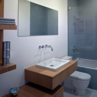Bild på ett mellanstort funkis brun brunt badrum för barn, med ett nedsänkt handfat, släta luckor, skåp i ljust trä, träbänkskiva, ett platsbyggt badkar, en dusch/badkar-kombination, en toalettstol med hel cisternkåpa, grå kakel, glaskakel, beige väggar, klinkergolv i porslin och vitt golv