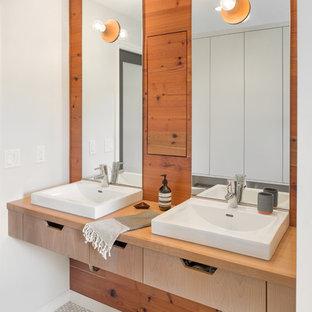 ポートランドの小さい北欧スタイルのおしゃれなマスターバスルーム (オーバーカウンターシンク、フラットパネル扉のキャビネット、淡色木目調キャビネット、木製洗面台、白い壁、モザイクタイル、ブラウンの洗面カウンター) の写真