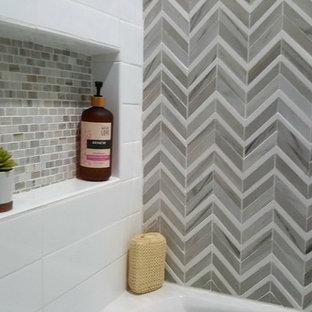 Foto di una stanza da bagno con doccia minimal di medie dimensioni con vasca ad alcova, vasca/doccia, WC sospeso, piastrelle multicolore, piastrelle a mosaico, pareti beige, pavimento in laminato, pavimento beige e doccia con tenda