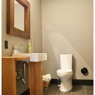 Modelo de cuarto de baño urbano, de tamaño medio, con armarios abiertos, puertas de armario beige, sanitario de dos piezas, baldosas y/o azulejos grises, baldosas y/o azulejos de cerámica, paredes grises, suelo de baldosas de cerámica, lavabo encastrado y encimera de madera