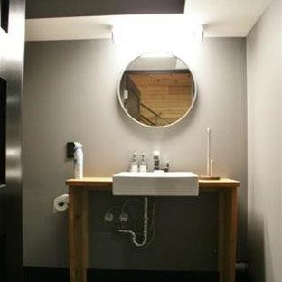 Неиссякаемый источник вдохновения для домашнего уюта: ванная комната среднего размера в стиле лофт с открытыми фасадами, бежевыми фасадами, раздельным унитазом, серой плиткой, керамической плиткой, серыми стенами, полом из керамической плитки, накладной раковиной и столешницей из дерева