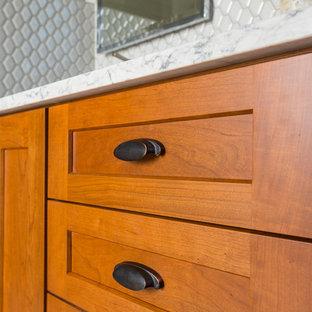 シンシナティの小さいおしゃれなマスターバスルーム (フラットパネル扉のキャビネット、中間色木目調キャビネット、アルコーブ型シャワー、一体型トイレ、白いタイル、磁器タイル、白い壁、磁器タイルの床、アンダーカウンター洗面器、珪岩の洗面台、グレーの床、開き戸のシャワー) の写真