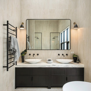 Design ideas for a contemporary master bathroom in Adelaide with furniture-like cabinets, dark wood cabinets, a freestanding tub, beige tile, beige walls, a vessel sink, marble benchtops, beige floor and white benchtops.