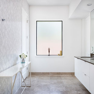 This is an example of a large contemporary master bathroom in Austin with flat-panel cabinets, white cabinets, gray tile, multi-coloured tile, white tile, mosaic tile, white walls, an undermount sink, travertine floors, solid surface benchtops and beige floor.