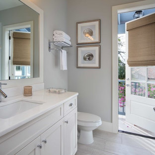 Beach style gray tile and porcelain tile porcelain tile bathroom photo in Orlando with an undermount sink, shaker cabinets, white cabinets and gray walls