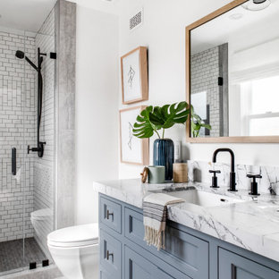 Transitional 3/4 white tile multicolored floor and single-sink alcove shower photo in Orange County with recessed-panel cabinets, gray cabinets, white walls, a hinged shower door and a built-in vanity