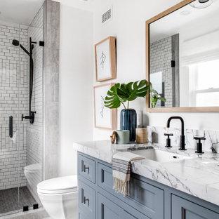 Inspiration för ett vintage badrum med dusch, med luckor med infälld panel, grå skåp, en dusch i en alkov, vit kakel, vita väggar, flerfärgat golv och dusch med gångjärnsdörr