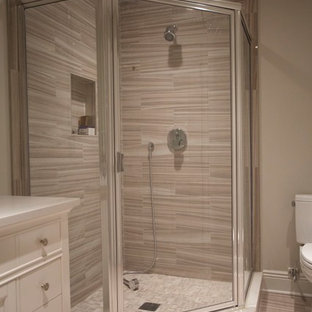 Corner shower - large traditional kids' beige tile, brown tile and porcelain tile porcelain tile and beige floor corner shower idea in New York with shaker cabinets, white cabinets, beige walls, an undermount sink and a hinged shower door