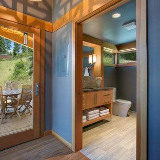 Modelo de cuarto de baño rústico, de tamaño medio, con armarios con paneles lisos, puertas de armario de madera clara, paredes beige, suelo de baldosas de porcelana, lavabo bajoencimera, encimera de cuarzo compacto y suelo beige