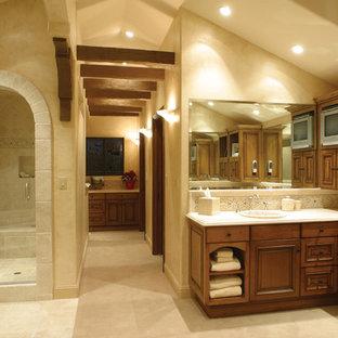 Foto de cuarto de baño mediterráneo con lavabo encastrado, armarios con paneles con relieve, puertas de armario de madera oscura, ducha empotrada, baldosas y/o azulejos beige y baldosas y/o azulejos de piedra