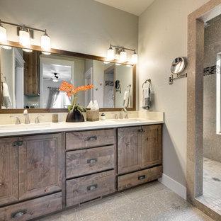 Imagen de cuarto de baño principal, rural, de tamaño medio, con armarios con paneles empotrados, puertas de armario de madera en tonos medios, ducha esquinera, baldosas y/o azulejos marrones, paredes grises, lavabo bajoencimera, encimera de cuarzo compacto, suelo gris, ducha abierta y encimeras blancas