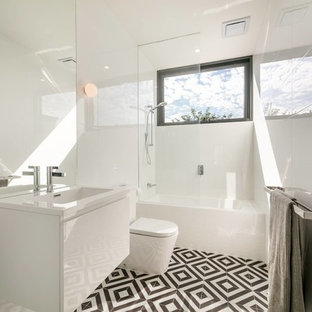 This is an example of a contemporary 3/4 bathroom in Melbourne with flat-panel cabinets, white cabinets, an alcove tub, a shower/bathtub combo, a wall-mount sink, black floor and white benchtops.