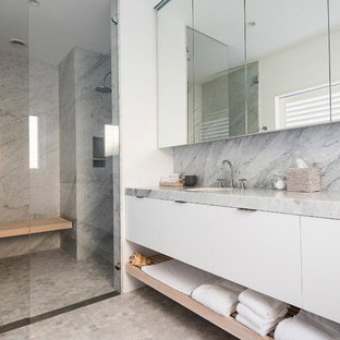 Beach style bathroom in Sydney with flat-panel cabinets, white cabinets, an alcove shower, gray tile, white walls, mosaic tile floors, an undermount sink, grey floor, a hinged shower door and grey benchtops.