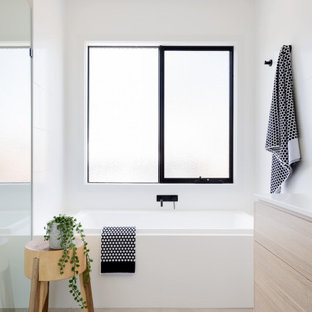 Photo of a contemporary bathroom in Melbourne with flat-panel cabinets, light wood cabinets, an alcove tub, white walls, grey floor and white benchtops.