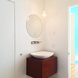 Ispirazione per una piccola stanza da bagno padronale moderna con lavabo a bacinella, ante lisce, ante rosse, vasca freestanding, WC sospeso, pareti bianche e parquet chiaro