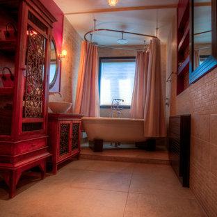 Diseño de cuarto de baño actual, de tamaño medio, con armarios tipo mueble, puertas de armario de madera oscura, bañera exenta, combinación de ducha y bañera, baldosas y/o azulejos beige, baldosas y/o azulejos de piedra, paredes marrones, suelo de cemento, lavabo sobreencimera y encimera de madera