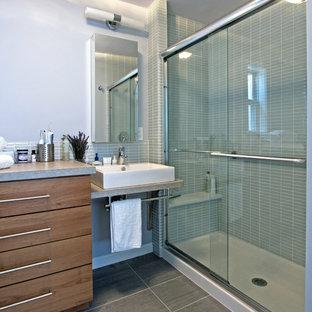 Esempio di una stanza da bagno contemporanea di medie dimensioni con lavabo a bacinella, ante lisce, top in laminato, doccia alcova, WC monopezzo, piastrelle grigie, piastrelle di vetro, pareti grigie, pavimento in gres porcellanato e ante in legno scuro