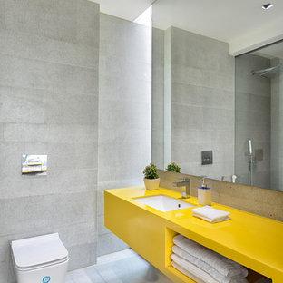 Modelo de cuarto de baño principal, actual, con armarios abiertos, puertas de armario amarillas, ducha esquinera, sanitario de pared, baldosas y/o azulejos grises, paredes grises, lavabo bajoencimera, suelo gris y encimeras amarillas