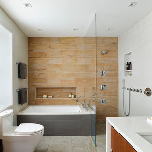 Design ideas for a medium sized modern ensuite bathroom in Philadelphia with flat-panel cabinets, medium wood cabinets, a submerged bath, a built-in shower, a one-piece toilet, orange tiles, stone tiles, grey walls, porcelain flooring, a submerged sink and engineered stone worktops.