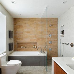 Foto på ett mellanstort funkis en-suite badrum, med släta luckor, skåp i mellenmörkt trä, ett undermonterat badkar, en kantlös dusch, en toalettstol med hel cisternkåpa, orange kakel, stenkakel, grå väggar, klinkergolv i porslin, ett undermonterad handfat och bänkskiva i kvarts